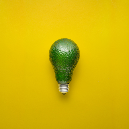 Creative concept photo of avocado as electric bulb on yellow background. Stock Photo