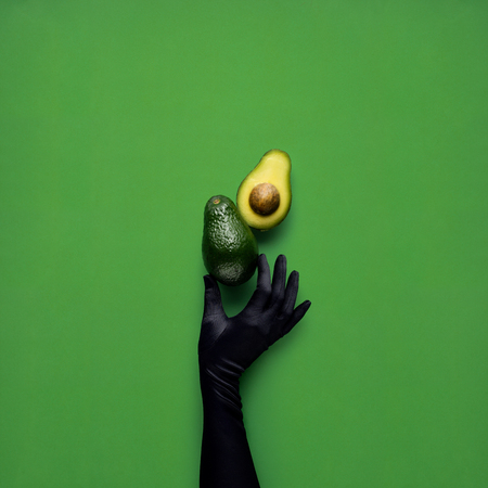 Creative concept photo of avocados with hand on green background. Stok Fotoğraf