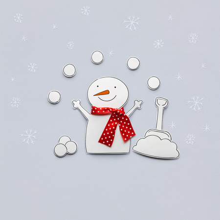 Creative photo of a snowman made of paper on grey background. Stock Photo