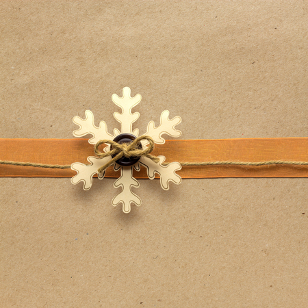 Creative christmas concept photo of a snowflake made of paper on brown background.