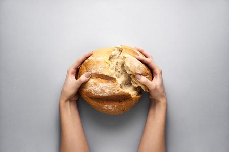 Photo de concept créatif des mains tenant du pain sur fond gris. Banque d'images - 97835559