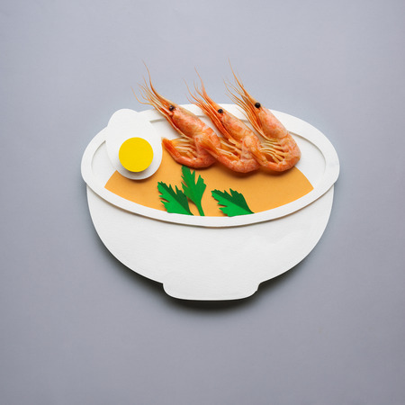 Creative concept photo of soup with shrimps made of paper on grey background.