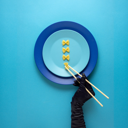 Creative concept photo of kitchenware with hand, painted plate with food on it on blue background.