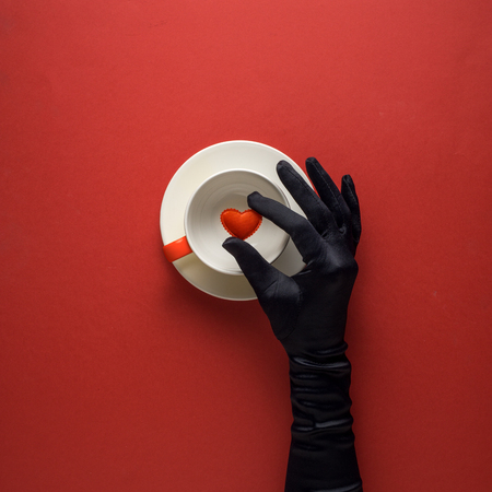 Creative concept photo of kitchenware with hand, painted plate with food on it on red background.