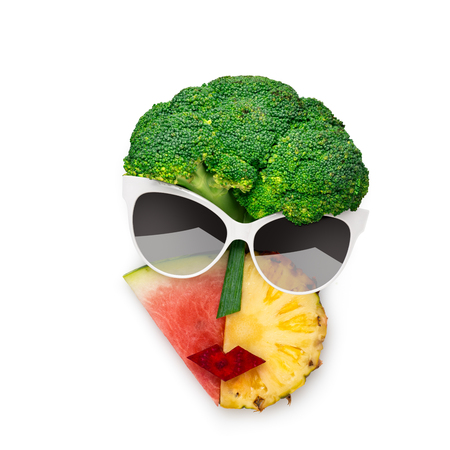 Creative concept photo of cubist style female face in sunglasses made of fruits and vegetables, on white background.