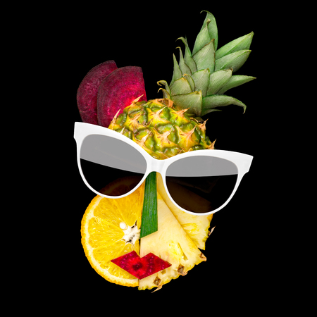 Creative concept photo of cubist style female face in sunglasses made of fruits and vegetables, on black background.