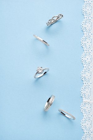 Creative concept photo of jewelry rings on blue background.