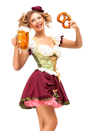 Creative concept photo of Oktoberfest waitress wearing a traditional Bavarian costume with beer and pretzel isolated on white background. Standard-Bild - 108418084