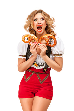Creative concept photo of Oktoberfest waitress wearing a traditional Bavarian costume with pretzels isolated on white background. Standard-Bild - 108418086