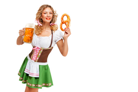 Creative concept photo of Oktoberfest waitress wearing a traditional Bavarian costume with beer and pretzel isolated on white background. Standard-Bild - 108418107