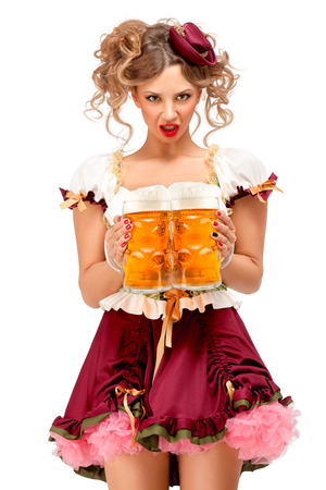 Creative concept photo of Oktoberfest waitress wearing a traditional Bavarian costume with beer isolated on white background. Standard-Bild - 108418108