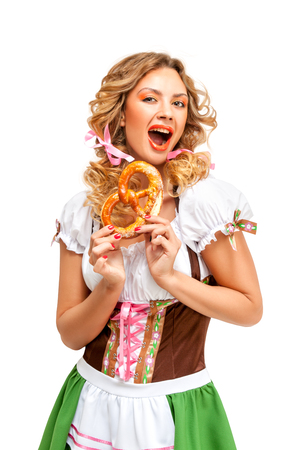 Creative concept photo of Oktoberfest waitress wearing a traditional Bavarian costume with pretzels isolated on white background. Standard-Bild