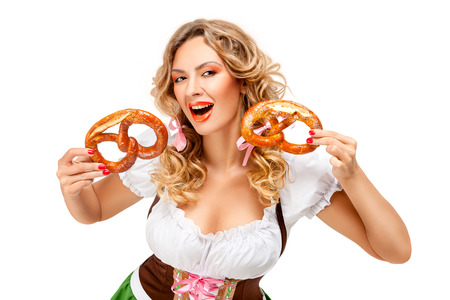 Creative concept photo of Oktoberfest waitress wearing a traditional Bavarian costume with pretzels isolated on white background. Standard-Bild - 108418438
