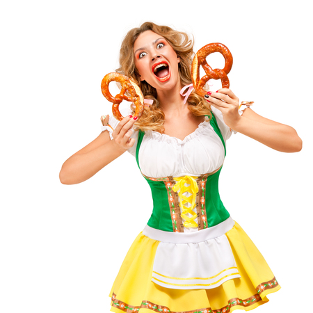 Creative concept photo of Oktoberfest waitress wearing a traditional Bavarian costume with pretzels isolated on white background. Standard-Bild - 108418446
