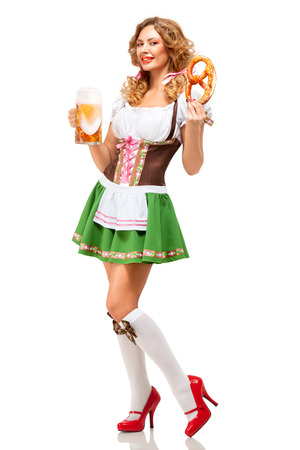 Creative concept photo of Oktoberfest waitress wearing a traditional Bavarian costume with beer and pretzel isolated on white background.