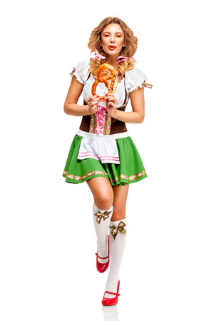 Creative concept photo of Oktoberfest waitress wearing a traditional Bavarian costume with pretzels isolated on white background. Standard-Bild - 108462191