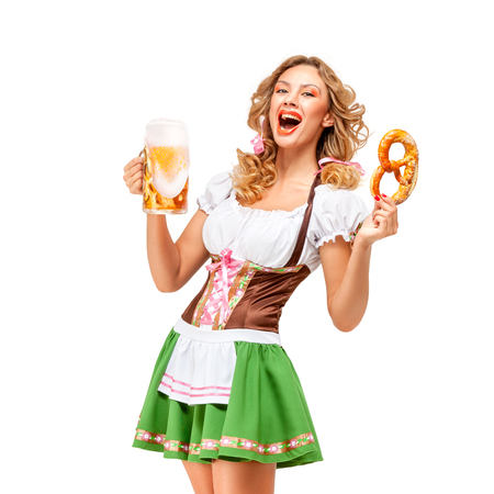 Creative concept photo of Oktoberfest waitress wearing a traditional Bavarian costume with beer and pretzel isolated on white background. Standard-Bild - 108462197