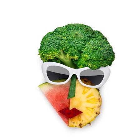 Foto de concepto creativo del rostro femenino de estilo cubista en gafas de sol hechas de frutas y verduras, sobre fondo blanco.