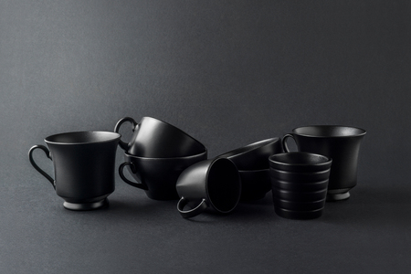 Creative concept photo of kitchenware, painted cups and mugs on black background. Stok Fotoğraf