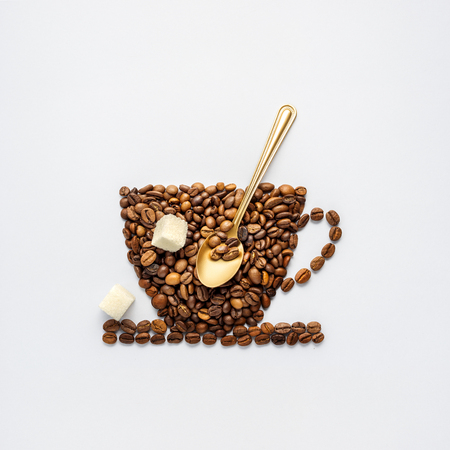 Creative concept photo of coffee cup made of beans with spoon and sugar on grey background. Stockfoto