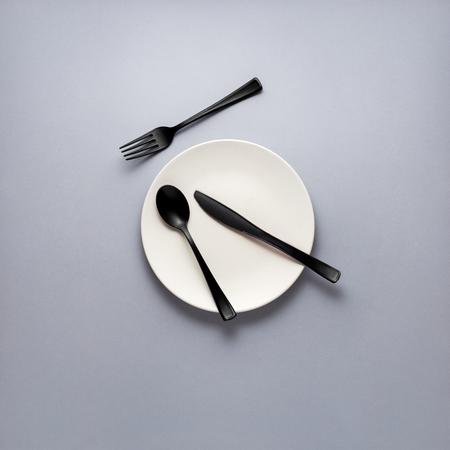 Concetto creativo foto di forchetta cucchiaio e coltello posa sulla piastra su sfondo grigio.