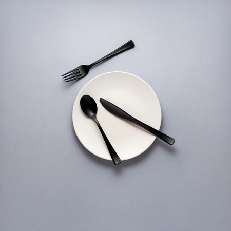 Creative concept photo of fork spoon and knife laying on plate on grey background. Stock Photo - 110125127
