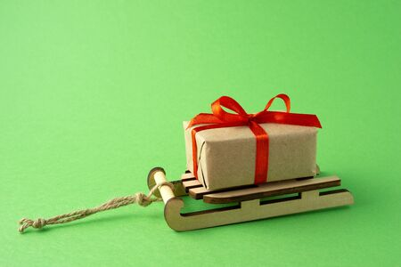 Creative concept still life Christmas holiday photo of sleigh with present gift box on green  background.