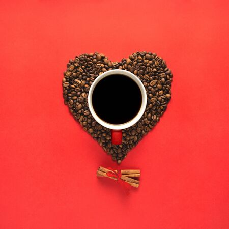Creative concept still life valentine day holiday photo of espresso coffee cup mug drink beverage with heart made of beans seeds and cinnamon on red background. 版權商用圖片