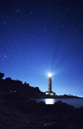 Night landscape with lighthouse and stars photo
