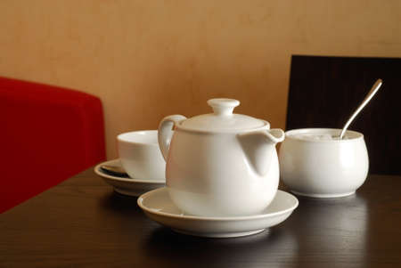 Teapot with cup in a restaurant interior