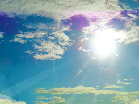 Sunrays on blue sky with clouds background photo