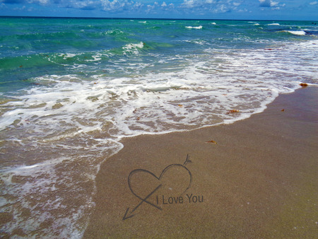 Vivid beach background with heart love on sand