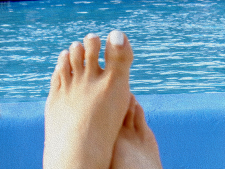 Beautiful pedicured woman feet on pool photo