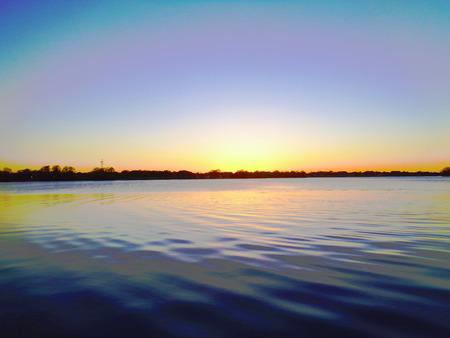 La puesta del sol en el lago ondula el agua