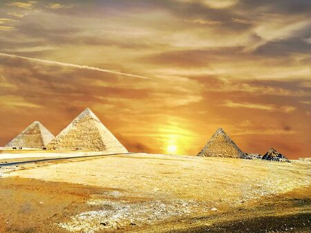 The Pyramids of Giza Cairo in Egypt during a golden sunset summer in the desert. Beautiful image picture background template