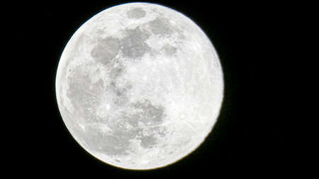 Big full moon on black background template picture image photographed through April 10, 2020. Orlando Florida USA.