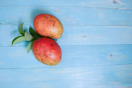 Mangoes on a blue wood table picture background template 写真素材