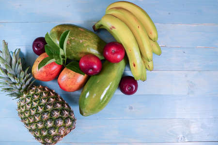Tropical Fruit as banana apple mangoes papaya pineapple on light blue wood picture image background template 写真素材
