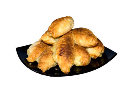 Pies from a shortcake dough laid out by a hill on a black plate, are isolated on a white background.