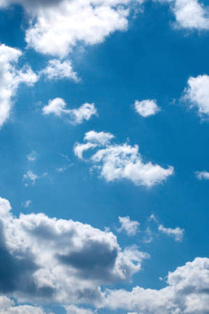 Small white clouds in the dark blue sky