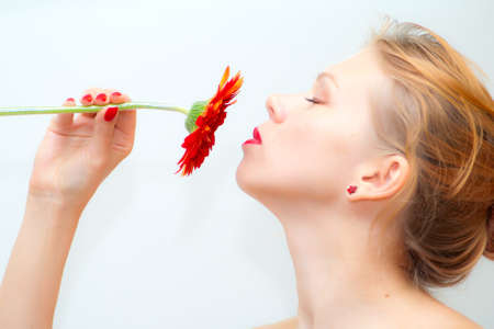 Portrait of beautiful young woman smelling red daisy photo