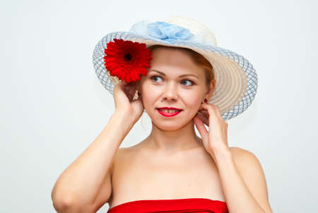 Attrective young girl in a straw hat and with a flower Gerbera photo