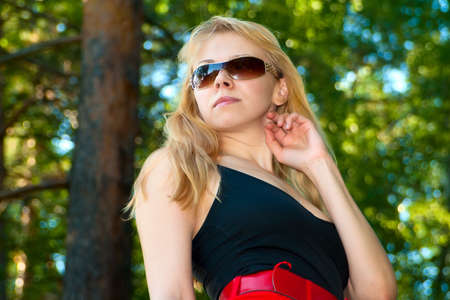 Portrait of the attractive young girl in sun glasses against green woo