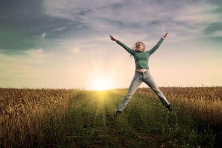 excitment: Retrato de saltar las mujeres jóvenes en jeans en campo de trigo  Foto de archivo