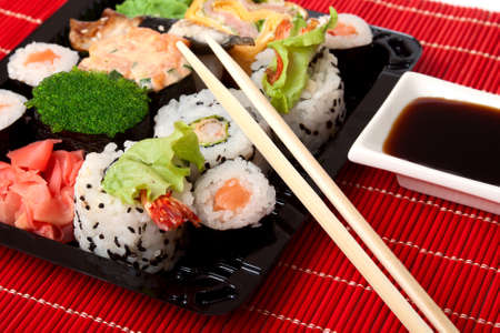 Sushi, sauce and wood chopstick on red bamboo napkin