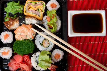Sushi, sauce and chopstick on a red bamboo napkin. Series japanese food