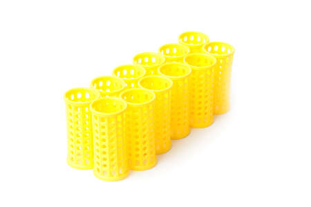 Few yellow Hair curlers on a white background