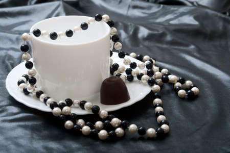 Abstraction of luxury. The black and white pearls lie on a white saucer with cup of coffee. A background a black soft leather photo