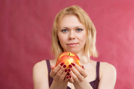 Portrait of beautiful woman with red apple on a red burgundy background