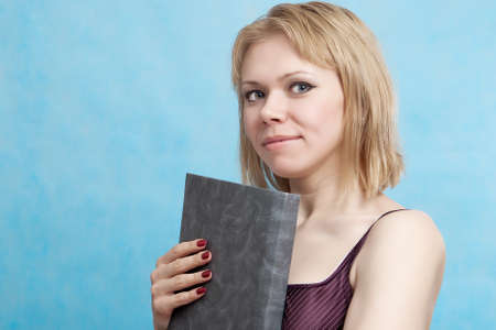 Young beautiful woman with  book on a blue background